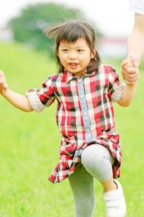 両親と手をつないでスキップする女の子の写真素材 [FYI02000427]