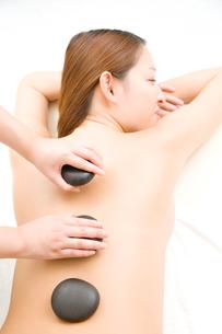 ストーンセラピーを受ける女性の写真素材 [FYI02000472]