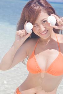 海辺で貝がらを持つ笑顔の水着女性の写真素材 [FYI02000521]