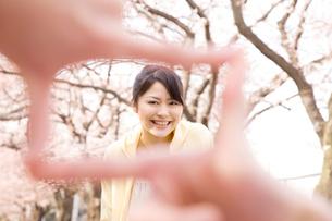指で作ったフレームの中で微笑む女性の写真素材 [FYI02000582]