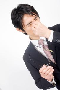 目頭を抑えているビジネスマンの写真素材 [FYI02000595]