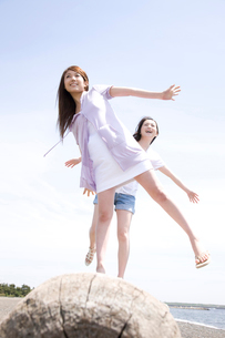 丸太の上を歩いて遊ぶ女性2人の写真素材 [FYI02000596]