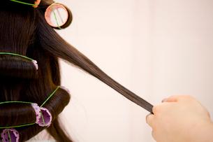 ヘアサロンで女性の髪にパーマをかける美容師の手元の写真素材 [FYI02000620]