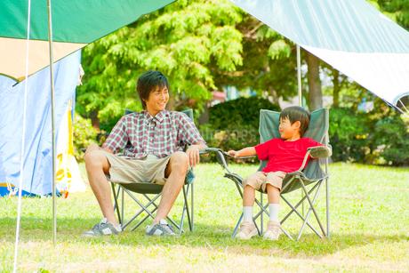 キャンプ場で椅子に座って談笑する父親と息子の写真素材 [FYI02000624]