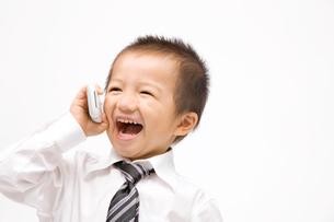 携帯電話で会話をする男の子の写真素材 [FYI02000687]