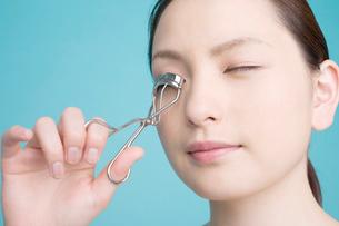 ビューラーで睫毛を整える女性の写真素材 [FYI02000723]
