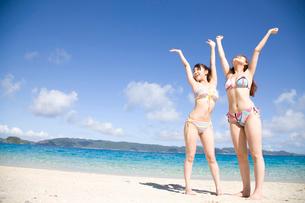 浜辺で万歳をしている水着姿の女性2人の写真素材 [FYI02000734]