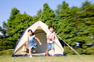 テントから駆け出してくる兄妹の写真素材 [FYI02000761]