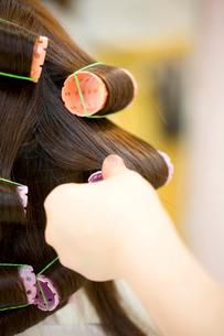 女性の髪にパーマをかける美容師の手元の写真素材 [FYI02000767]