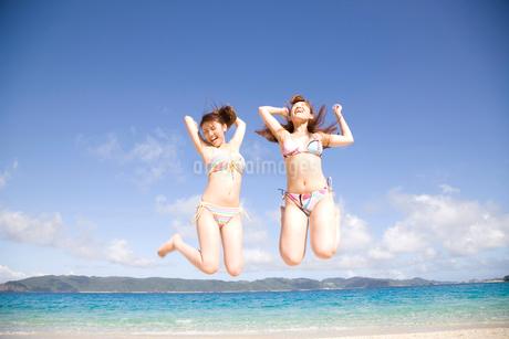 浜辺でジャンプする水着を着た2人の女性の写真素材 [FYI02000822]