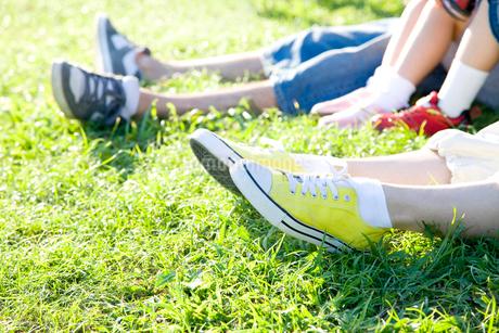 芝生に寝転ぶ家族の足元の写真素材 [FYI02000900]