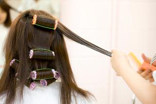 美容師にパーマをかけてもらう女性の後ろ姿の写真素材 [FYI02000925]
