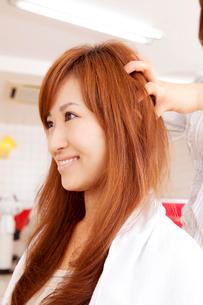 美容師にヘッドマッサージをしてもらう女性の写真素材 [FYI02000942]