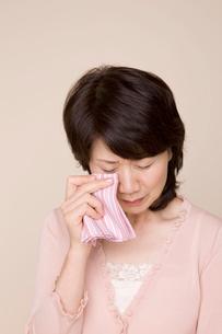 ハンカチで涙を拭くシニア女性の写真素材 [FYI02000969]