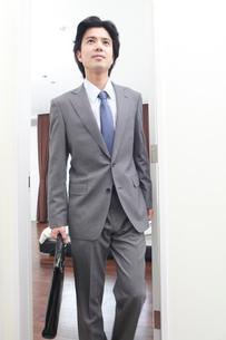 スーツを着て部屋を出る男性の写真素材 [FYI02000991]