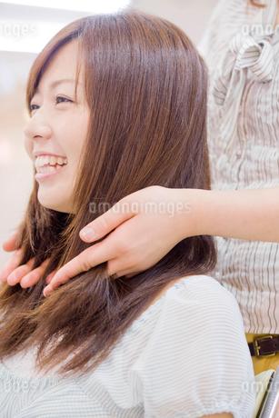 美容師に髪のカウンセリングを受ける女性の写真素材 [FYI02001023]