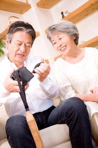 カメラの掃除をするシニア男性と微笑むシニア女性の写真素材 [FYI02001084]