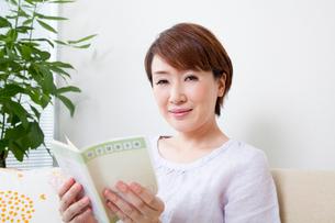 母子手帳を開いて微笑む妊婦の写真素材 [FYI02001111]