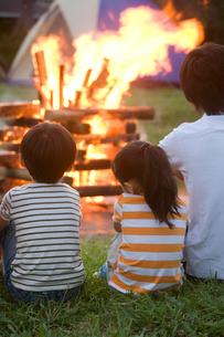 キャンプファイヤーを見る家族の後ろ姿の写真素材 [FYI02001243]