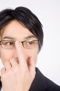 メガネを押さえるビジネスマンの写真素材 [FYI02001274]
