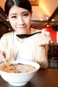 ラーメンを食べる女性客の写真素材 [FYI02001279]