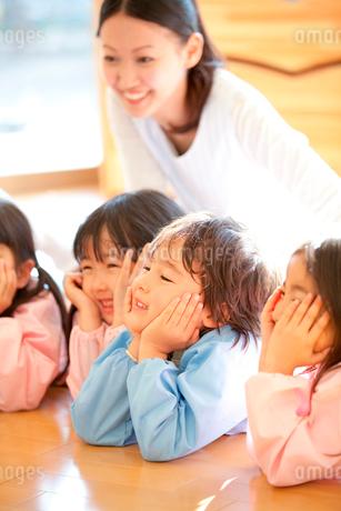 頬杖をついて微笑む幼稚園児と笑顔の幼稚園教諭の写真素材 [FYI02001334]