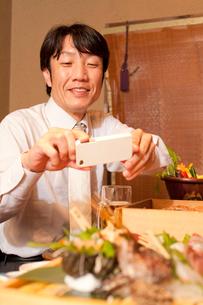 スマートフォンで料理を撮るビジネスマンの写真素材 [FYI02001348]