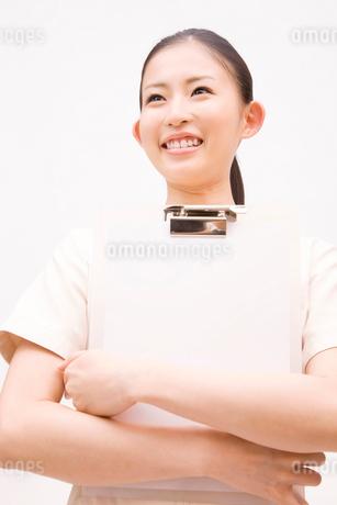 バインダーを持って微笑む歯科衛生士の写真素材 [FYI02001356]