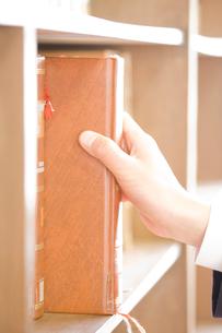図書室の本を手に取る男子中学生の手元の写真素材 [FYI02001375]