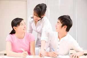 問題について話し合う中学生男女と塾講師の写真素材 [FYI02001380]