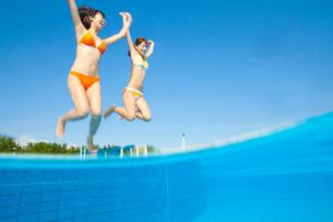 プールに跳びこむ水着姿の女性2人の写真素材 [FYI02001396]