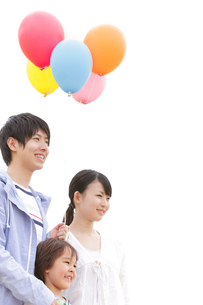風船を持って微笑む家族の写真素材 [FYI02001397]