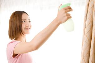 消臭スプレーをかける女性の写真素材 [FYI02001467]