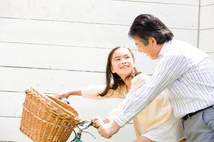 自転車に乗る孫を補助する祖父の写真素材 [FYI02001519]