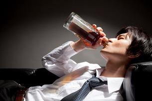ウィスキーをラッパ飲みするビジネスマンの写真素材 [FYI02001534]
