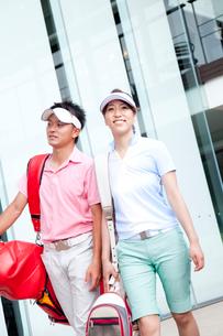 ゴルフバッグを持って歩く男女の写真素材 [FYI02001554]