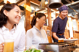 料理を運ぶ居酒屋店員と笑顔の女性客の写真素材 [FYI02001642]