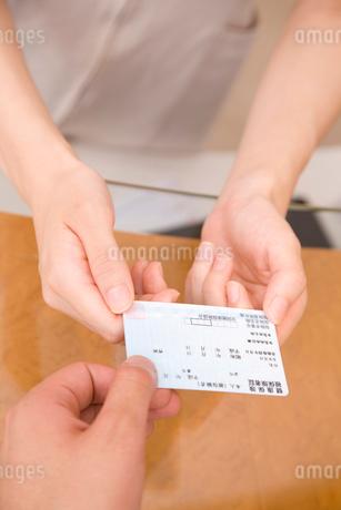 男性患者から保険証を受け取る歯科衛生士の手元の写真素材 [FYI02001654]