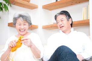 編み物をするシニア女性と笑顔のシニア男性の写真素材 [FYI02001838]
