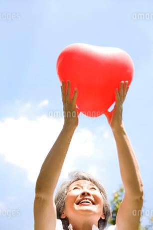 ハートの風船を持っているシニア女性の写真素材 [FYI02001863]