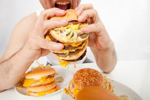 ハンバーガーを食べる中年男性の写真素材 [FYI02001865]