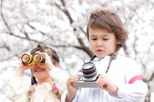 双眼鏡を覗く女の子とカメラを持つ男の子の写真素材 [FYI02001915]