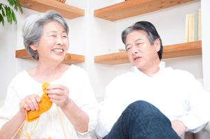 編み物をするシニア女性と笑顔のシニア男性の写真素材 [FYI02001932]