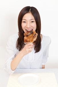 骨付き肉を食べる女性の写真素材 [FYI02001934]
