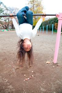 鉄棒で遊ぶ女の子の写真素材 [FYI02002054]