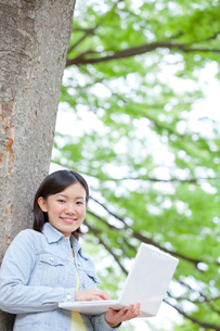 木にもたれノートパソコンを操作する女子大生の写真素材 [FYI02002055]