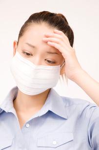 マスクをつけて頭を抑えている女性の写真素材 [FYI02002141]