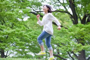 笑顔でスキップする女子大生の写真素材 [FYI02002191]