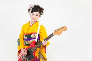 エレキギターを持ち微笑む振袖姿の女性の写真素材 [FYI02002192]