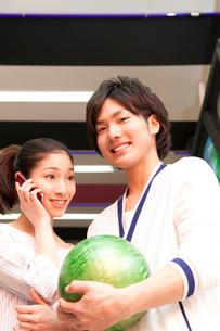 ボウリング球を持つ男性とスマートフォンで話す女性の写真素材 [FYI02002354]